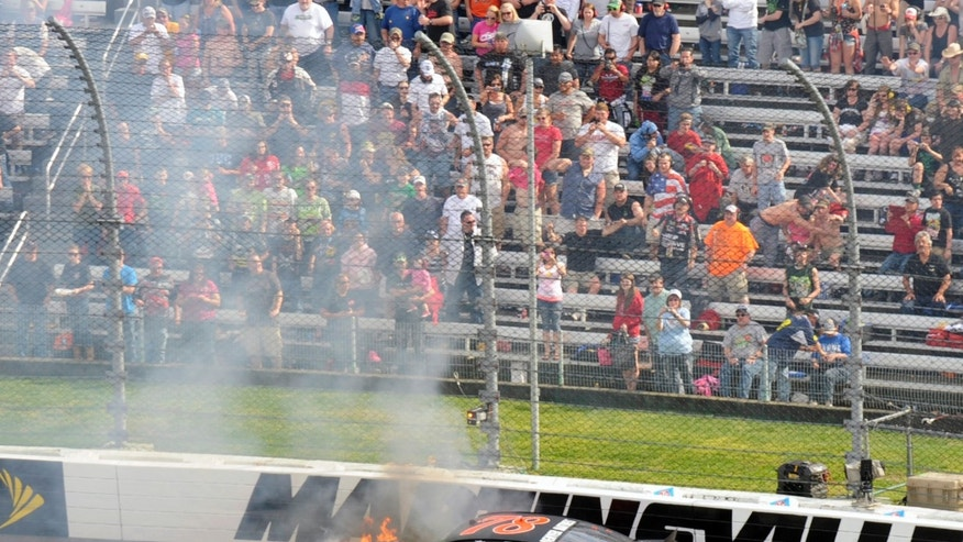 Kurt Busch's car burns after he hit the wall in the first turn during the STP 500 NASCAR Sprint Cup series auto race at Martinsville Speedway in Martinsville, Va., Sunday, April 7, 2013.  (AP Photo/Don Petersen)