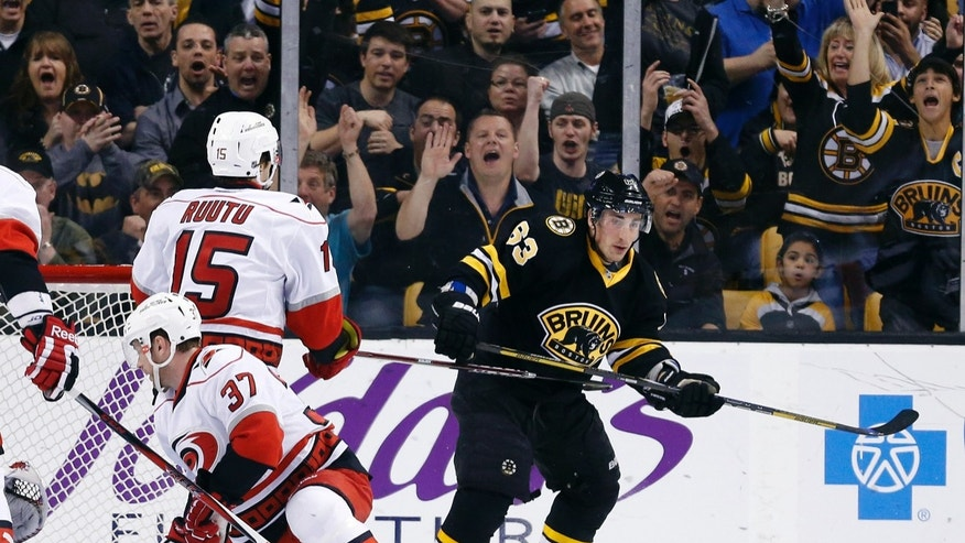 Boston Bruins' Brad Marchand (63) pivots away from Carolina Hurricanes' Tim Brent (37) and Tuomo Ruutu (15) after scoring his second goal in the first period of an NHL hockey game in Boston, Monday, April, 8, 2013. (AP Photo/Michael Dwyer)