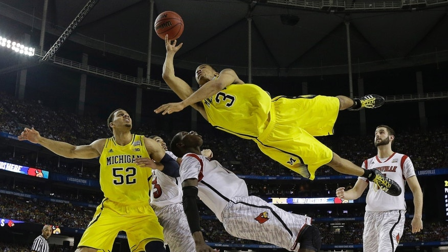 Michigan guard Trey Burke (3) shoots over Louisville center Gorgui Dieng (10) during the second half of the NCAA Final Four tournament college basketball championship game Monday, April 8, 2013, in Atlanta. (AP Photo/Charlie Neibergall)
