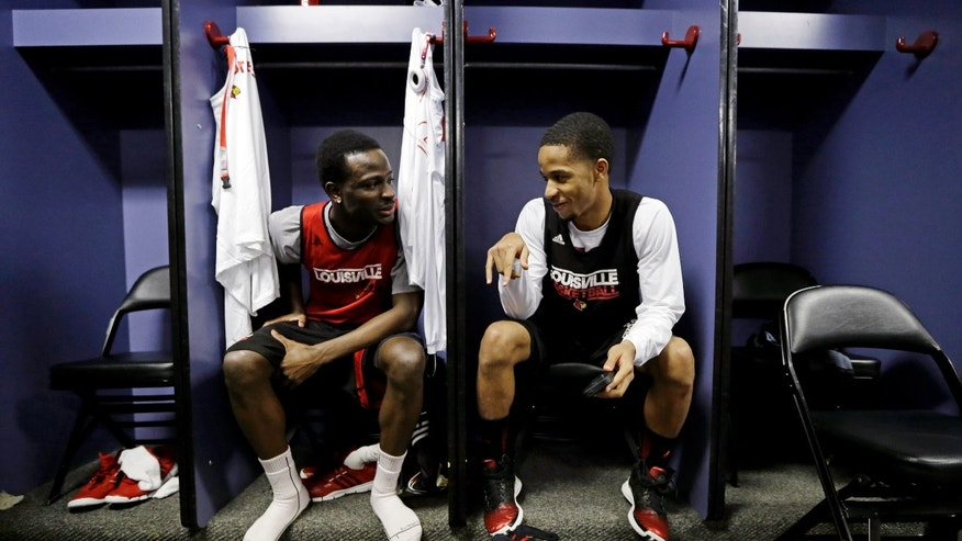 Louisville's Michael Baffour, left, and Jordan Bond chat in the locker room before practice for their NCAA Final Four tournament college basketball game Sunday, April 7, 2013, in Atlanta. Louisville plays Michigan in the championship game on Monday. (AP Photo/Charlie Neibergall)