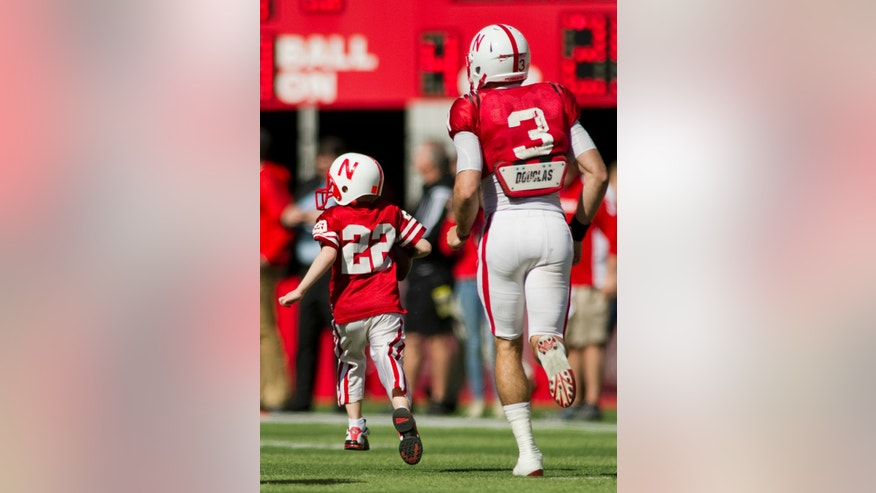 CORRECTS JACK HOFFMAN AGE TO 7, NOT 6 AS ORIGINALLY SENT - Nebraska's Taylor Martinez (3) guides seven-year-old Jack Hoffman, of Atkinson, Neb., down the field for his touchdown play during a special segment dedicated to Hoffman during the second half of the Red-White Spring Game Saturday, April 6, 2013, at Memorial Stadium. Hoffman, of Atkinson has won the hearts of fans and everyone in the football program for his courageous bout with brain cancer.  (AP Photo/Lincoln Journal Star, Matt Ryerson)