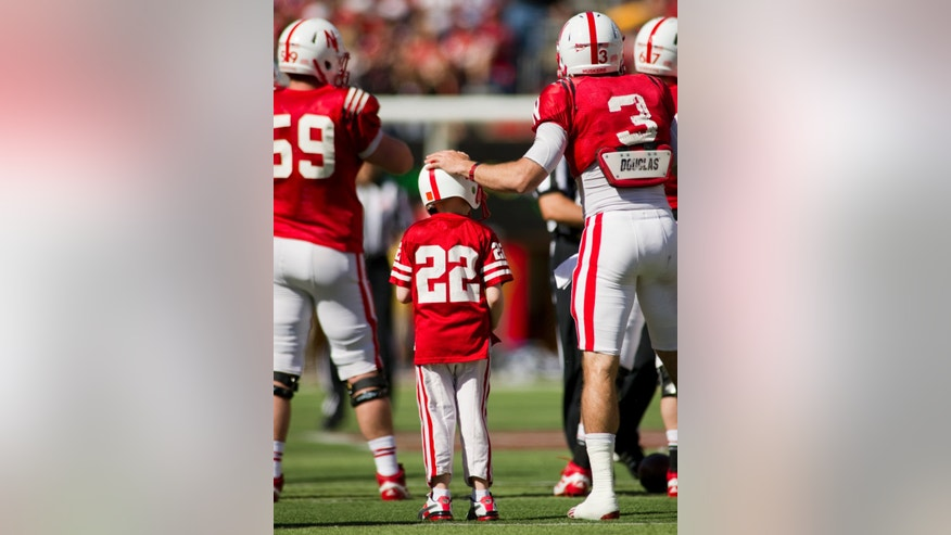CORRECTS AGE OF JACK HOFFMAN TO 7, NOT 6 AS ORIGINALLY SENT - Nebraska's Taylor Martinez (3) prepares seven-year-old Jack Hoffman, of Atkinson, Neb., for his touchdown play during a special segment dedicated to Hoffman during the second half of the Red-White Spring Game Saturday, April 6, 2013, at Memorial Stadium. Since 2011 Hoffman has been struggling with seizures and complications related to a brain tumor. (AP Photo/Lincoln Journal Star, Matt Ryerson)
