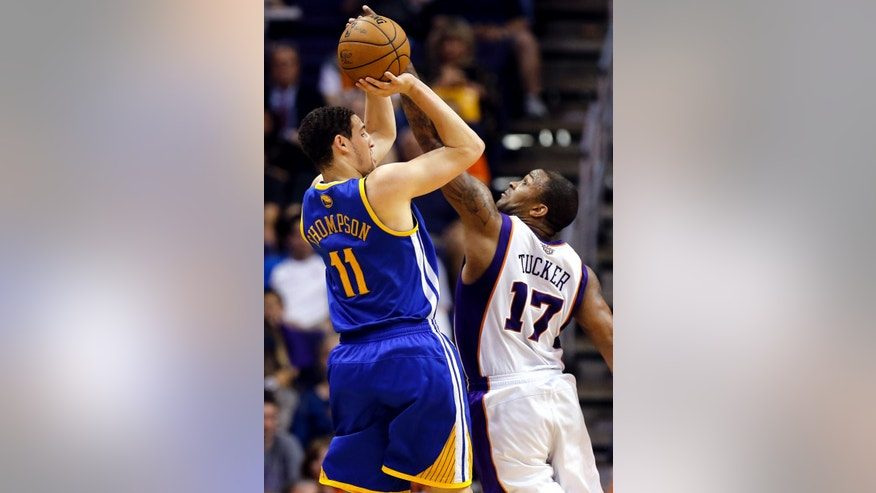 Golden State Warriors' Klay Thompson (11) shoots over Phoenix Suns' P.J. Tucker (17) during the second half of an NBA basketball game, Friday, April 5, 2013, in Phoenix. The Warriors won 111-107. (AP Photo/Matt York)