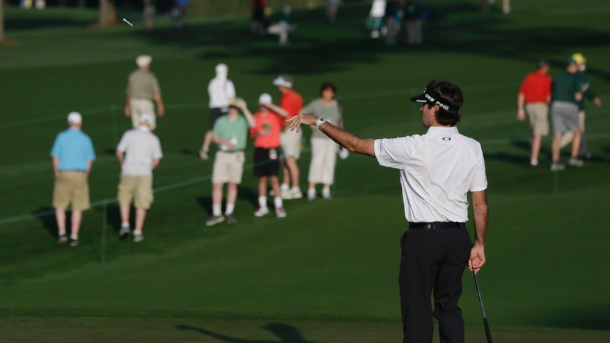 Bubba Watson throws a tee to his caddie on the second hole during a practice round for the Masters golf tournament Tuesday, April 9, 2013, in Augusta, Ga. (AP Photo/Darron Cummings)