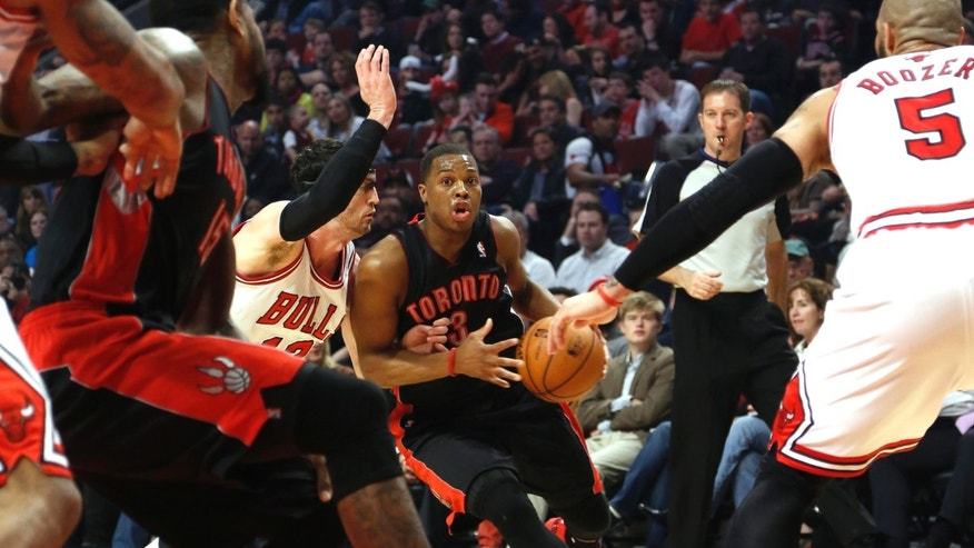 Toronto Raptors' Kyle Lowry looks for an opening as he drives past the Chicago Bulls' Kirk Hinrich during the first quarter in an NBA basketball game on Tuesday, April 9, 2013 in Chicago. (AP Photo/Charles Cherney)