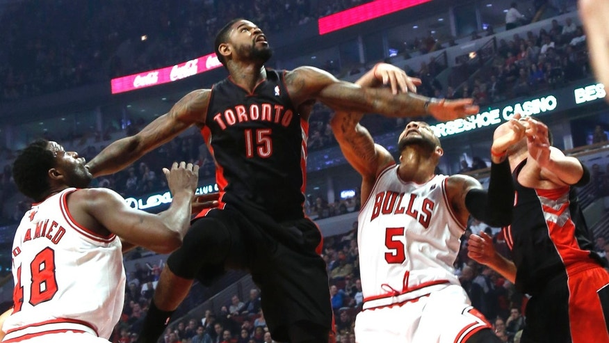 Toronto Raptors' Amir Johnson leaps above Chicago Bulls  players Nazr Mohammed and Carlos Boozer trying to get a rebound during the first quarter in an NBA basketball game on Tuesday, April 9, 2013 in Chicago. (AP Photo/Charles Cherney)