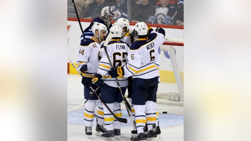 Buffalo Sabres players celebrate after Kevin Porter (12) scored on Winnipeg Jets goaltender Ondrej Pavelec (31) during the third period of their NHL hockey game in Winnipeg, Manitoba, Tuesday, April 9, 2013. The Jets won 4-1. (AP Photo/The Canadian Press, Trevor Hagan)