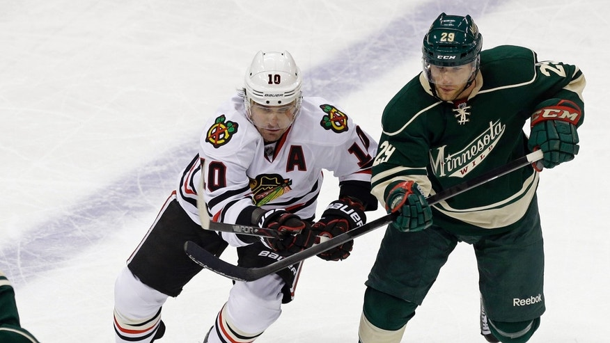 Chicago Blackhawks' Patrick Sharp, left, making his return to the ice, and new Minnesota Wild player Jason Pominville, chase the puck in the first period of an NHL hockey game Tuesday, April 9, 2013 in St. Paul. Sharp has returned to the Chicago Blackhawks' lineup after a 14-game absence because of a shoulder injury.  (AP Photo/Jim Mone)