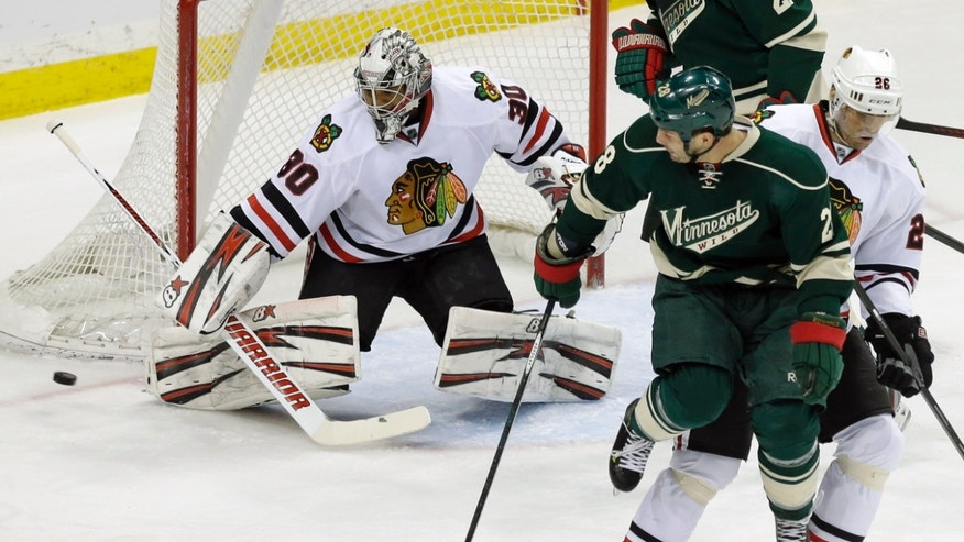 Minnesota Wild's Zenon Konopka, second from right, jumps to make way for a shot which went wide of Chicago Blackhawks goalie Ray Emery in the first period of an NHL hockey game Tuesday, April 9, 2013 in St. Paul.At right is Blackhawks' Michael Handzus.  (AP Photo/Jim Mone)