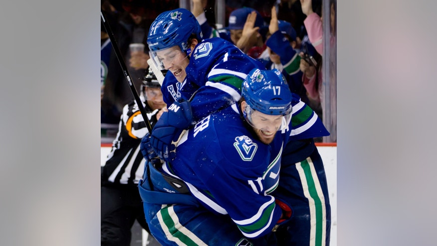 Vancouver Canucks' Ryan Kesler, right, and Mason Raymond celebrate Kesler's goal against the Phoenix Coyotes during the first period of an NHL hockey game in Vancouver, British Columbia, on Monday April 8, 2013. (AP Photo/The Canadian Press, Darryl Dyck)
