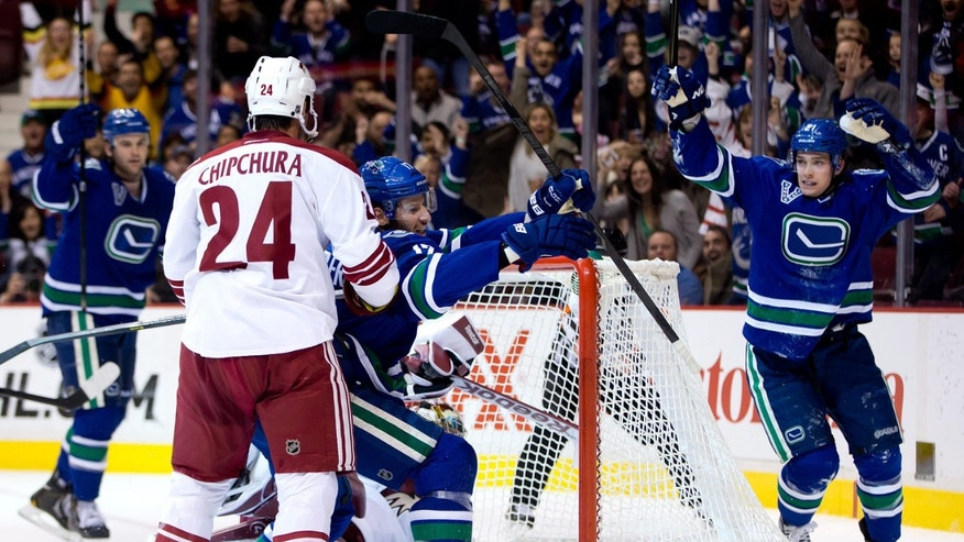 Vancouver Canucks' Ryan Kesler, center, Mason Raymond, right, and Zack Kassian, far left celebrate Kesler's goal as Phoenix Coyotes' Kyle Chipchura (24) watches during the first period of an NHL hockey game in Vancouver, British Columbia, on Monday April 8, 2013. (AP Photo/The Canadian Press, Darryl Dyck)