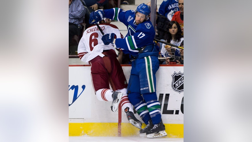 Vancouver Canucks' Ryan Kesler, right, checks Phoenix Coyotes' David Schlemko during the first period of an NHL hockey game in Vancouver, British Columbia, on Monday April 8, 2013. (AP Photo/The Canadian Press, Darryl Dyck)