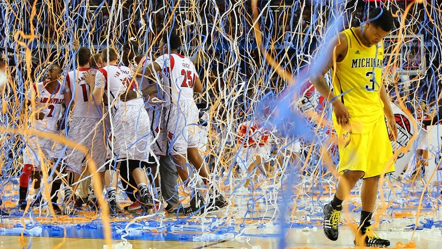 Michigan guard Trey Burke (3) walks off the court as confetti falls on Louisville players, including Russ Smith (2), Luke Hancock (11), Stephan Van Treese (44) and Zach Price (25), after the NCAA Final Four tournament college basketball championship game, Monday, April 8, 2013, in Atlanta. Louisville won 82-76. (AP Photo/Atlanta Journal-Constitution, Curtis Compton)
