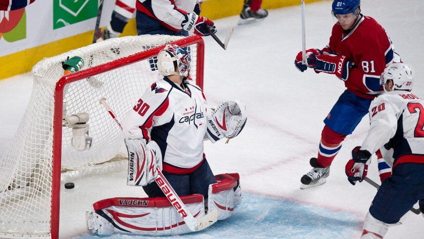 Montreal Canadiens' Lars Eller scores past Washington Capitals goalie Michal Neuvirth as Capitals' Troy Brouwer looks on during first period NHL hockey action Tuesday, April 9, 2013 in Montreal.  (AP Photo/The Canadian Press, Paul Chiasson)