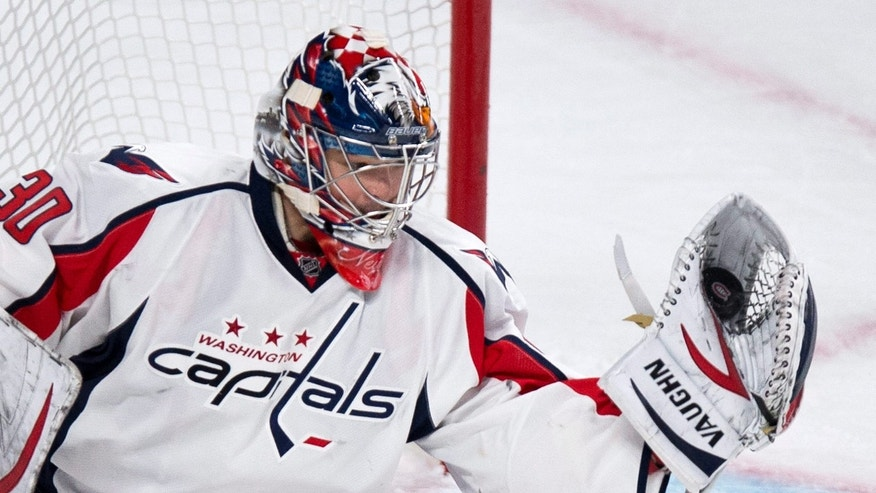 Washington Capitals goalie Michal Neuvirth makes a glove save as they face the Montreal Canadiens during first period NHL hockey action Tuesday, April 9, 2013 in Montreal.  (AP Photo/The Canadian Press, Paul Chiasson)
