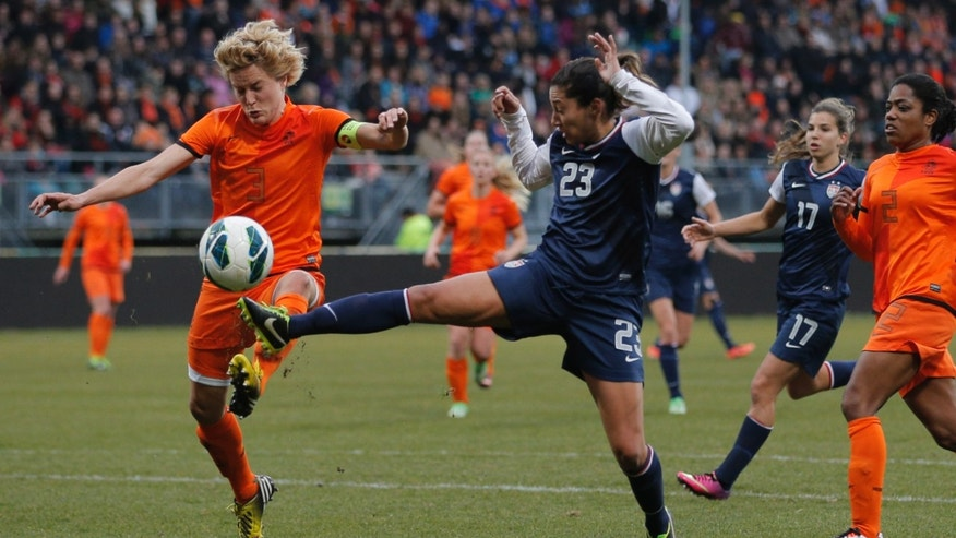 Christen Press of the U.S., center with number 23, and Daphne Koster of The Netherlands, left, vie for the ball during the international friendly women's soccer match at ADO The Hague stadium, Netherlands, Tuesday April 9, 2013. (AP Photo/Peter Dejong)