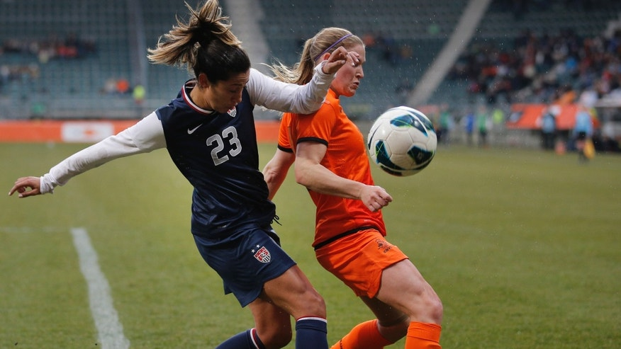 Christen Press of the U.S., left, and Claudia van den Heiligenberg of The Netherlands, right, vie for the ball during the international friendly women's soccer match at ADO The Hague stadium, Netherlands, Tuesday April 9, 2013. (AP Photo/Peter Dejong)