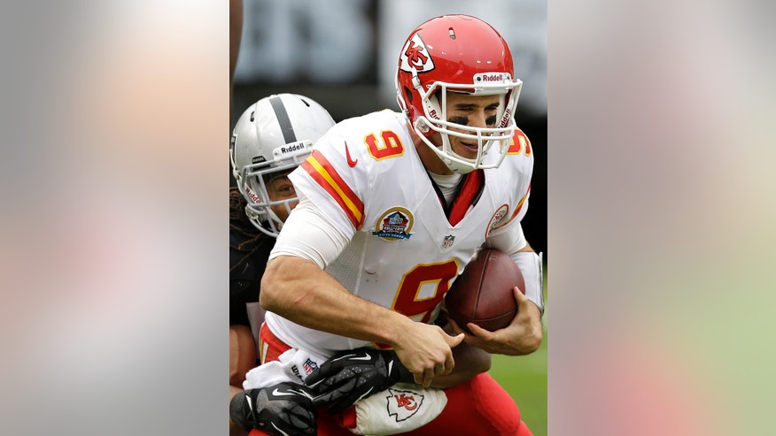 FILE - In this Dec. 16, 2012, file photo, Kansas City Chiefs quarterback Brady Quinn (9) is sacked by Oakland Raiders linebacker Philip Wheeler during the second quarter of an NFL football game in Oakland, Calif. Quinn is the new backup quarterback for the Seattle Seahawks after agreeing to terms with the club. The deal was announced by the team on Tuesday, April 9, 2013. (AP Photo/Marcio Jose Sanchez, File)