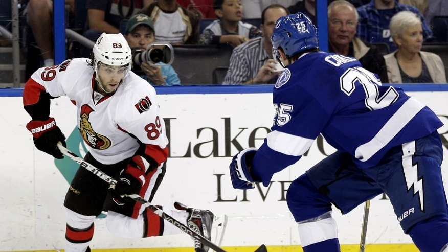 Ottawa Senators left wing Cory Conacher (89) controls the puck in front of Tampa Bay Lightning defenseman Matt Carle (25) during the first period of an NHL hockey game Tuesday, April 9, 2013, in Tampa, Fla. (AP Photo/Chris O'Meara)