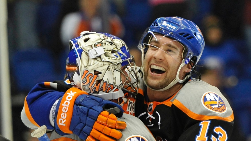 New York Islanders' Colin McDonald (13) hugs goalie Evgeni Nabokov (20) after the Islanders defeated the Tampa Bay Lightning 4-2 in an NHL hockey game Saturday, April 6, 2013, at Nassau Coliseum in Uniondale, N.Y. (AP Photo/Kathy Kmonicek)