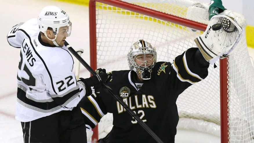 Dallas Stars goalie Kari Lehtonen (32) catches the puck in front of Los Angeles Kings center Trevor Lewis (22) during the first period of an NHL hockey game Tuesday, April 9, 2013, in Dallas. (AP Photo/LM Otero)
