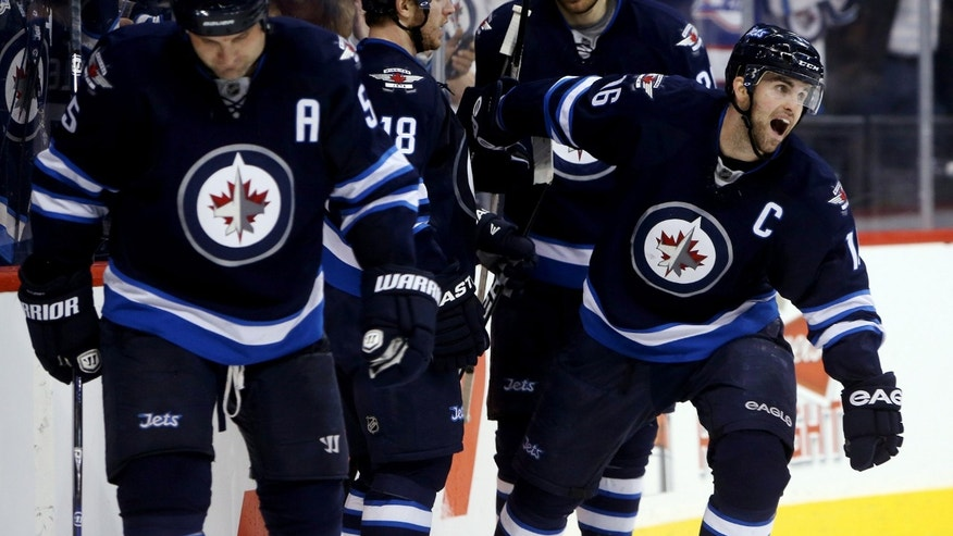 Winnipeg Jets' Mark Stuart (5), Bryan Little (18), Blake Wheeler (26) and Andrew Ladd (16) celebrate after Ladd scored against the Buffalo Sabres during the second period of their NHL hockey game in Winnipeg, Manitoba, Tuesday, April 9, 2013. (AP Photo/The Canadian Press, Trevor Hagan)