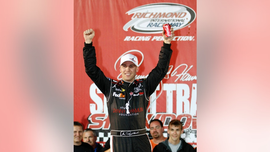 FILE - In this April 28, 2011 file photo, Denny Hamlin celebrates after winning the Denny Hamlin Foundation Short Track Showdown auto race at Richmond International Raceway in Richmond, Va. Hamlin won't compete in his annual charity race at home track Richmond because of the back injury that has sidelined him for at least a month.  (AP Photo/Steve Helber, File)