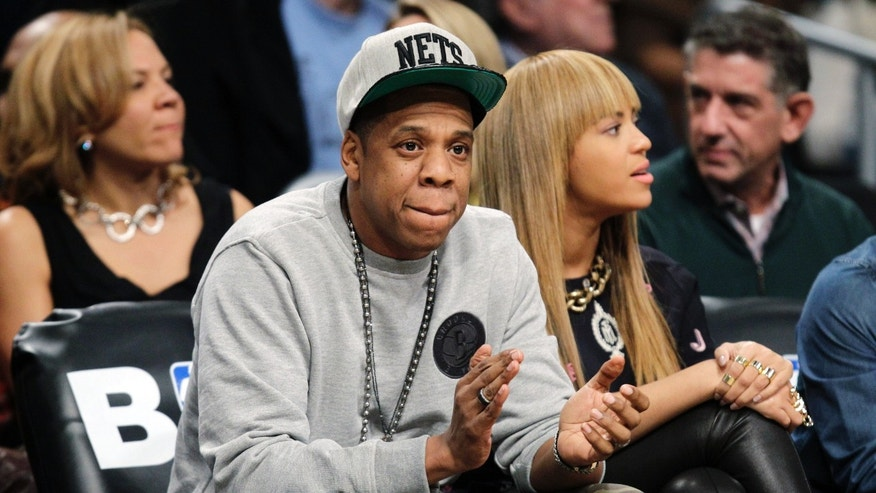 In this Nov. 26, 2012, file photo, rap mogul and Brooklyn Nets minority owner Jay-Z and his wife, Beyonce, watch an NBA basketball game between the Nets and the New York Knicks at Barclays Center in New York. Jay -Z is selling his stake in the Nets so he can become certified as a player agent, possibly before the end of the season.