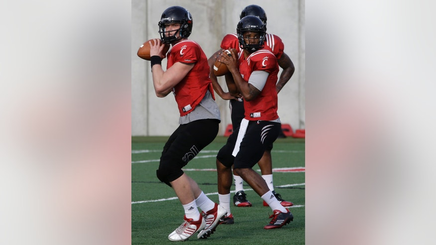 Cincinnati quarterbacks Brendon Kay, left, and Munchie Legaux, right, drop back to pass during the team's final spring NCAA college football practice, Wednesday, April 10, 2013, in Cincinnati. (AP Photo/Al Behrman)