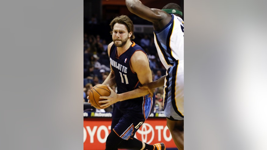 Charlotte Bobcats' Josh McRoberts (11) moves the ball under Memphis Grizzlies' Zach Randolph during the first half of an NBA basketball game in Memphis, Tenn., Tuesday, April 9, 2013. (AP Photo/Danny Johnston)