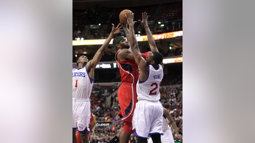 Atlanta Hawks' Josh Smith, center, shoots as Philadelphia 76ers' Nick Young (1) and Thaddeus Young (21) defend in the first half of an NBA basketball game, Wednesday, April 10, 2013, in Philadelphia. (AP Photo/H. Rumph Jr)