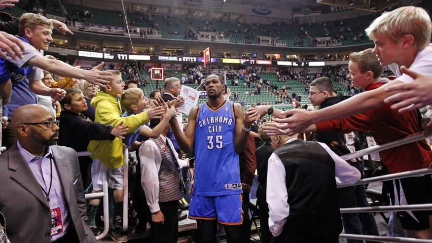 Fans reach for Oklahoma City Thunder's Kevin Durant (35) at the end of an NBA basketball game against the Utah Jazz, Tuesday, April 9, 2013, in Salt Lake City. The Thunder won 90-80. (AP Photo/Rick Bowmer)