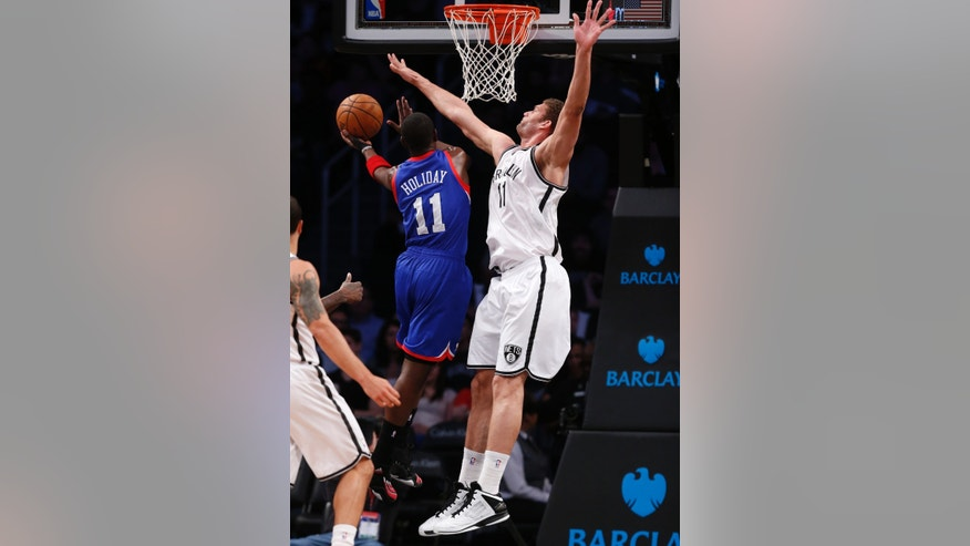Brooklyn Nets center Brook Lopez (11) defends as Philadelphia 76ers forward Evan Turner (12) goes up for a layup in the first half of an NBA basketball game, Tuesday, April 9, 2013, in New York. (AP Photo/Kathy Willens)