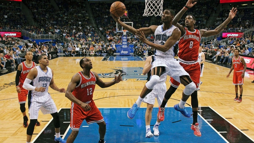 Orlando Magic's Maurice Harkless, center, shoots in front of Milwaukee Bucks' Larry Sanders (8) as Luc Richard Mbah a Moute (12), of Cameroon, and Magic's Tobias Harris, left, watch during the first half of an NBA basketball game, Wednesday, April 10, 2013, in Orlando, Fla. (AP Photo/John Raoux)