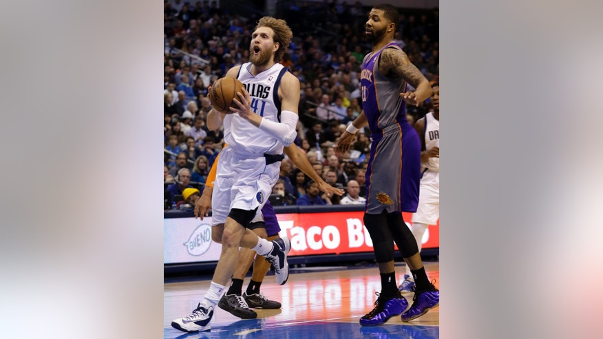 Dallas Mavericks forward Dirk Nowitzki (41), of Germany, drives past Phoenix Suns forward Markieff Morris (11) during the first half of an NBA basketball game, Wednesday, April 10, 2013, in Dallas. (AP Photo/LM Otero)