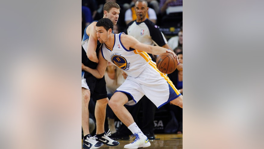 Golden State Warriors' Klay Thompson (11) drives for the basket against Minnesota Timberwolves' Luke Ridnour during the first half of an NBA basketball game, Tuesday, April 9, 2013, in Oakland, Calif. (AP Photo/George Nikitin)