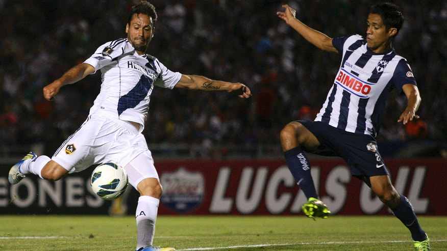 L.A. Galaxy's Todd Dunivant, left, prepares to kick a shot as Monterrey's Severo Meza attempts to block during a CONCACAF Champions League semi-final soccer match in Monterrey, Mexico, Wednesday, April 10, 2013. (AP Photo/Alfredo Lopez, JAM MEDIA)