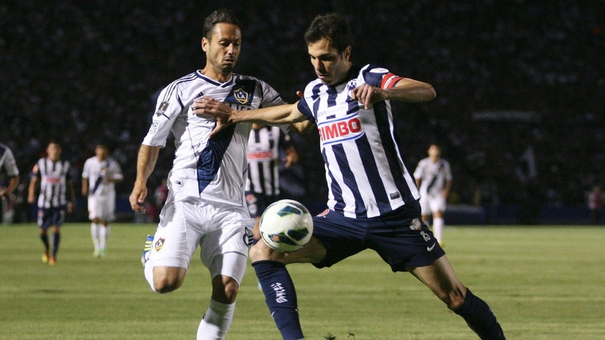 L.A. Galaxy's Marcelo Fazzio, left, fights for the ball with Monterrey's Jose Maria Basanta at a CONCACAF Champions League semi-final soccer match in Monterrey, Mexico, Wednesday, April 10, 2013. (AP Photo/Alfredo Lopez, JAM MEDIA)