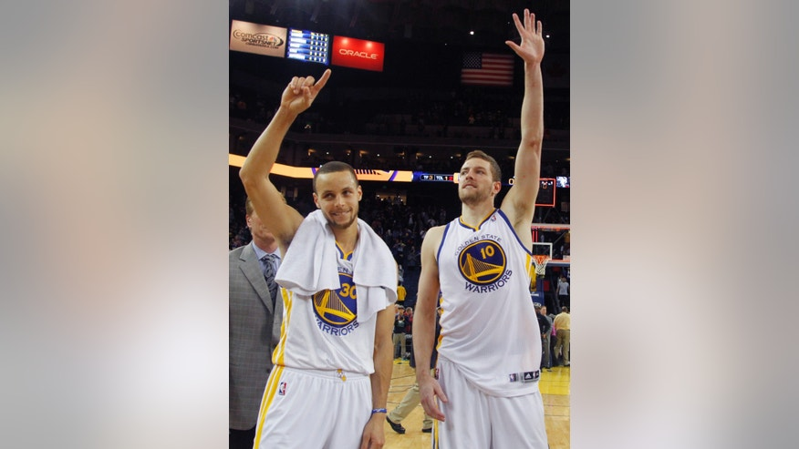 Golden State Warriors' Stephen Curry, left, and David Lee wave to the fans after the Warriors beat Minnesota Timberwolves 105-89, Tuesday, April 9, 2013 in Oakland, Calif. The Warriors clinched a berth in the NBA playoffs after today's win. (AP Photo/George Nikitin)