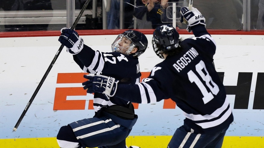 Yale right wing Andrew Miller (17) celebrates his winning goal against UMass Lowell with Kenny Agostino (18) during overtime of an NCAA Frozen Four college hockey semifinal in Pittsburgh, Thursday, April 11, 2013. Yale won 3-2. (AP Photo/Gene J. Puskar)