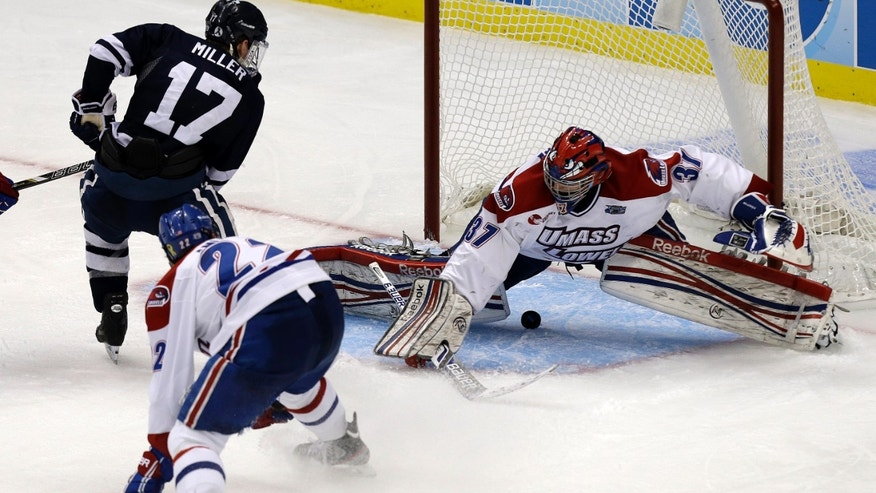 Yale right wing Andrew Miller (17) slips the puck between the legs of UMass Lowell goalie Connor Hellebuyck for the winning goal during overtime of an NCAA Frozen Four college hockey game in Pittsburgh, Thursday, April 11, 2013. Yale won 3-2. (AP Photo/Gene J. Puskar)