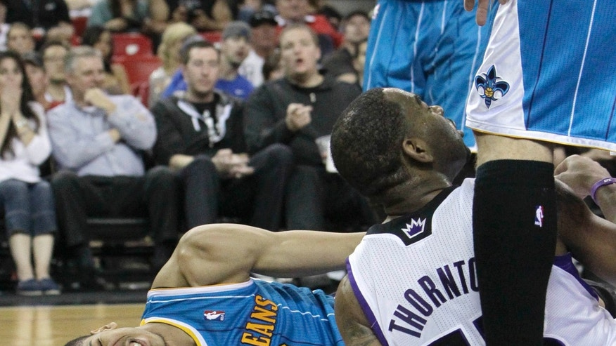 New Orleans Hornets forward Anthony Davis, left, grimaces in pain after he was charged into by Sacramento Kings guard Marcus Thornton during the fourth quarter of an NBA basketball game in Sacramento, Calif., Wednesday, April 10, 2013.   Davis injured his knee and had to leave the game. The Kings won 121-110.(AP Photo/Rich Pedroncelli)