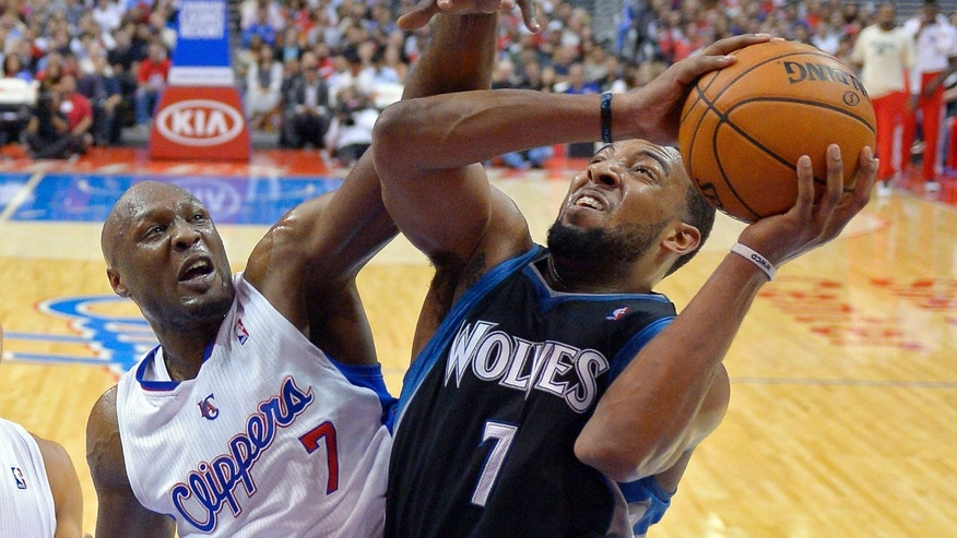 Minnesota Timberwolves forward Derrick Williams, right, shoots against Los Angeles Clippers forward Lamar Odom during the first half of their NBA basketball game, Wednesday, April 10, 2013, in Los Angeles. (AP Photo/Mark J. Terrill)