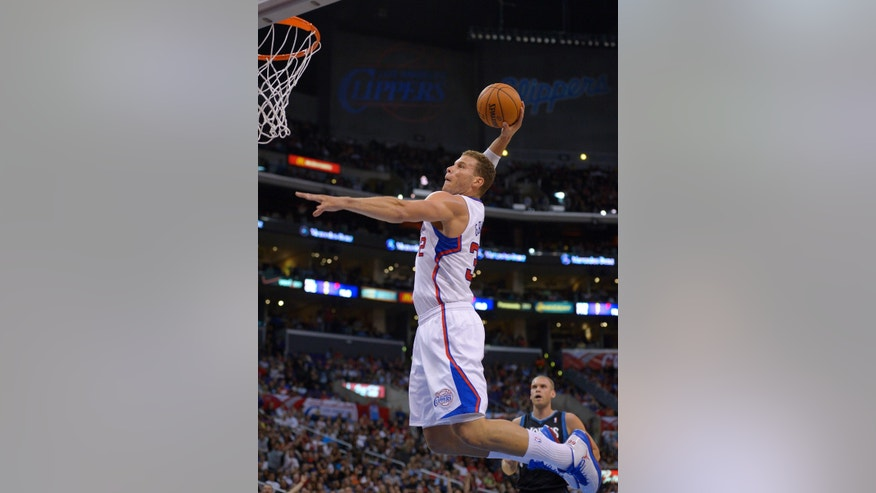 Los Angeles Clippers forward Blake Griffin, left, dunks as Minnesota Timberwolves center Greg Stiemsma watches during the first half of their NBA basketball game, Wednesday, April 10, 2013, in Los Angeles. (AP Photo/Mark J. Terrill)