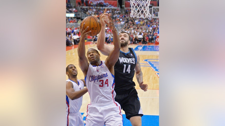 Los Angeles Clippers guard Willie Green, center, and Minnesota Timberwolves center Nikola Pekovic, of Montenegro, , right, go after a rebound as guard Chris Paul looks on during the first half of their NBA basketball game, Wednesday, April 10, 2013, in Los Angeles. (AP Photo/Mark J. Terrill)