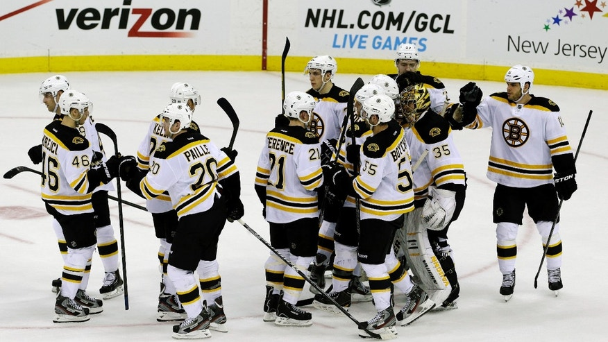Boston Bruins players celebrate after defeating the New Jersey Devils 5-4 in an NHL hockey game, Wednesday, April 10, 2013, in Newark, N.J. (AP Photo/Julio Cortez)