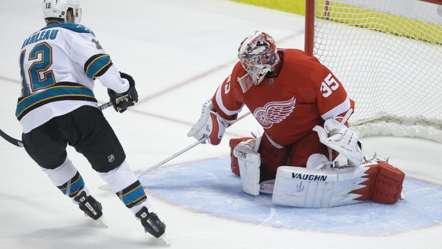 San Jose Sharks center Patrick Marleau (12) shoots past the defense of Detroit Red Wings goalie Jimmy Howard and scores during the shootout of an NHL hockey game in Detroit, Thursday, April 11, 2013. The Sharks won 3-2. (AP Photo/Carlos Osorio)