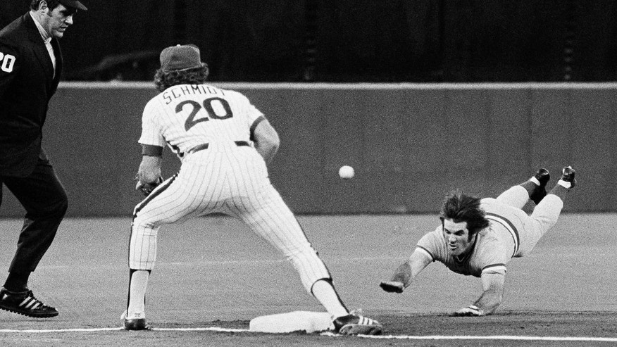 ADVANCE FOR WEEKEND EDITIONS, APRIL 13-14 - FILE - In this June 20, 1977, file photo, Cincinnati Reds' Pete Rose slides head first into third base for a triple as Philadelphia Phillies Mike Schmidt fields the late throw during a baseball game in Philadelphia. Baseball's all-time hits leader got his start on climbing up the list 50 years ago this week, when he made his big-league debut for the Reds in Cincinnati on April 8, 1963. )AP Photo/Rusty Kennedy)