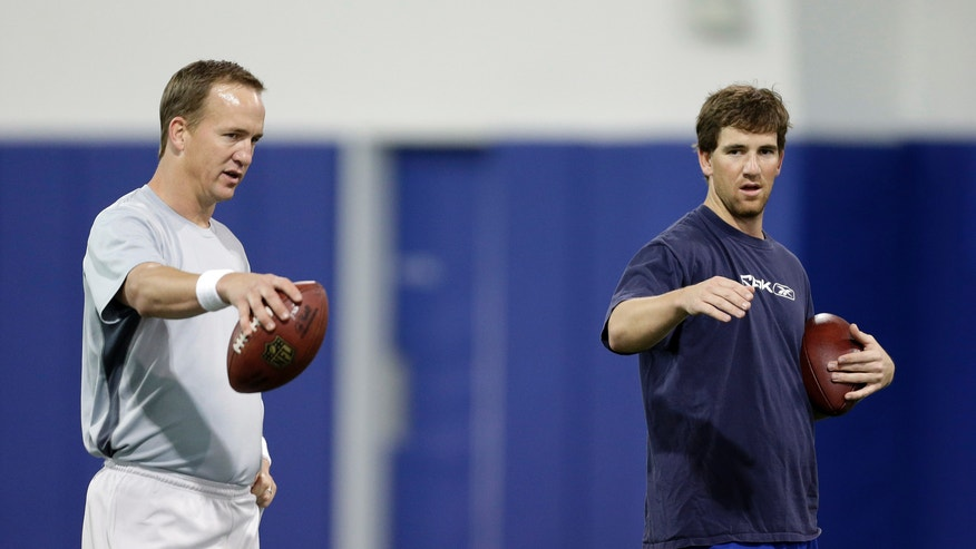 Denver Broncos quarterback Peyton Manning, left, and brother Eli Manning, quarterback for the New York Giants, talk during football workouts at Duke University in Durham, N.C., Thursday, April 11, 2013. (AP Photo/Gerry Broome)
