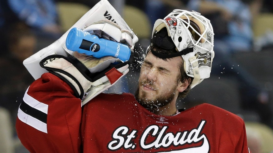 St. Cloud State goalie Ryan Faragher squirts water in his face after allowing a goal during the first period of an NCAA college hockey Frozen Four semifinal game against Quinnipiac in Pittsburgh, Thursday, April 11, 2013. (AP Photo/Gene J. Puskar)